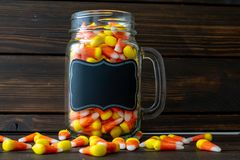 Halloween background frame consisting of a jar full of candy corn on a dark wooden table with a black table that you can personali royalty free stock photo