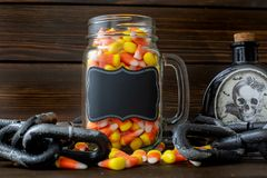 Halloween background frame with a jar of candy corn on a wooden table surrounded by a dark chain and next to a vial of poison and stock photos