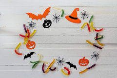 Halloween background with frame of jelly worms, paper pumpkins a Royalty Free Stock Photo
