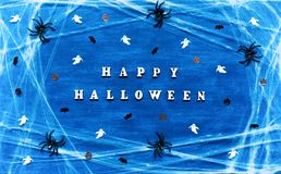 Halloween background. Happy Halloween letters with spider web, spiders and Halloween decorations Stock Photos