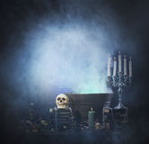 Halloween background of a lot of witchcraft tools. Halloween background with a lot of different witchcraft tools: scull, candles, book, poison and smoke Stock Photos