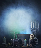 Halloween background of a lot of witchcraft tools. Halloween background with a lot of different witchcraft tools: scull, candles, book, poison and smoke Royalty Free Stock Photography
