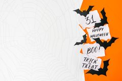 Halloween background, mockup. Card with text HAPPY HALLOWEEN, BO. O, TRICK OR TREAT, 31 and paper black bats on orange and white background with copy space stock images
