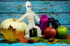 Halloween background with mummy,spider and autumn  decoration. Halloween background - mummy, lilac candle, white pumpkin, green and red apple , black spider and Royalty Free Stock Photography