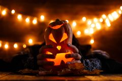 Halloween background with pumpkin and witch hands. On wooden table against grunge bokeh lights background Stock Photos
