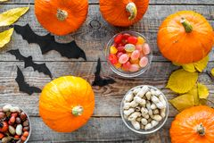 Halloween background. Pumpkins, paper bats and autumn leaves on wooden background top view.  Stock Photo
