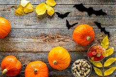 Halloween background. Pumpkins, paper bats and autumn leaves on wooden background top view copyspace. Halloween background. Pumpkins, paper bats and autumn Stock Image