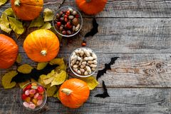 Halloween background. Pumpkins, paper bats and autumn leaves on wooden background top view copyspace. Halloween background. Pumpkins, paper bats and autumn Stock Photo