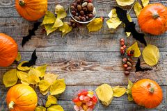 Halloween background. Pumpkins, paper bats and autumn leaves on wooden background top view copyspace. Halloween background. Pumpkins, paper bats and autumn Royalty Free Stock Image
