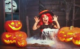 halloween barnflickahäxa som förbereder dryck i kittel med p Arkivfoton