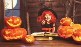 halloween barnhäxa med pumpastålar och den magiska boken av s Arkivbild