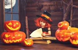 halloween barnhäxa med pumpastålar och den magiska boken av s Arkivfoto