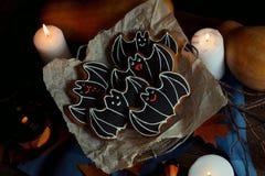 Halloween batte i biscotti di zucchero con le decorazioni, le candele di luce ed il vecchio fondo di legno Fotografia Stock Libera da Diritti