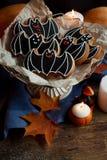 Halloween batte i biscotti di zucchero con le decorazioni, le candele di luce ed il vecchio fondo di legno Foto verticale Fotografia Stock Libera da Diritti