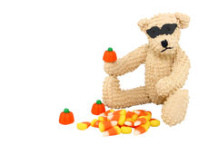 Halloween Bear. A cute little teddy bear wears a black mask while enjoying his favorite fall candies, mallow pumpkins and candy corn Stock Photography
