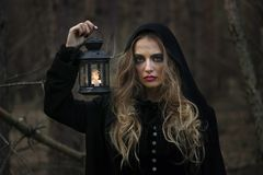 Halloween. beautiful girl with a lantern in a black dress in the forest. Stock Photo