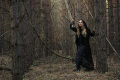 Halloween. beautiful girl with a lantern in a black dress in the forest. Stock Images