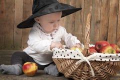 Halloween behandla som ett barn med korgen av äpplen Arkivbild