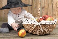 Halloween behandla som ett barn med korgen av äpplen Arkivbilder