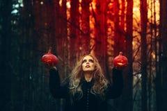 Halloween bella ragazza con una zucca in un vestito nero nella foresta fotografie stock libere da diritti