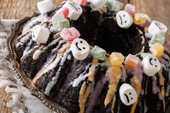 Halloween black Bundt cake decorated with candied fruits, marshm Stock Image