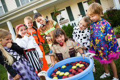 Halloween: Bobbing for Apple Game. Group of neighborhood children on Halloween, having fun in costume trick-or-treating and playing games Royalty Free Stock Images