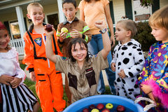Halloween: Bobbing for Apple Game. Group of neighborhood children on Halloween, having fun in costume trick-or-treating and playing games Stock Image