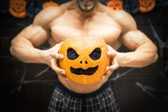 Halloween bodybuilder with pumpkin Stock Images