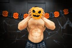 Halloween bodybuilder with pumpkin Stock Photos