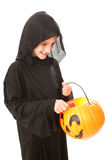 Halloween Boy with Candy. Little boy dressed in his halloween costume, taking a lollipop out of his pumpkin bucket. Isolated on white stock images