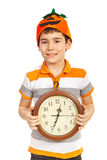 Halloween boy holding clock. Halloween boy with pumpkin hat holding clock isolated on white background Stock Photo