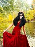 Halloween Brunettefrau mit Halloween-Schädelmake-up in einem roten d Lizenzfreie Stockfotos