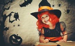 Halloween bruxa pequena alegre com conjur mágico da varinha e do livro Fotos de Stock Royalty Free