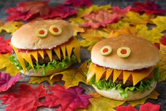 Halloween burger monsters on autumn leaves Royalty Free Stock Photos