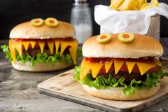 Halloween burger monsters with french fries on wood. En table Royalty Free Stock Photography