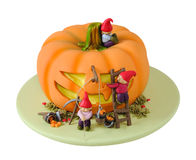 Halloween cake. Cute cartoon like cake with little gnomes cutting a halloween face out of a pumpkin. Cake is made with fondant sugar paste. Isolated on white Stock Photos