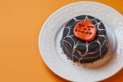 Halloween-cake in een witte plaat Oppervlakte oranje achtergrond Royalty-vrije Stock Afbeeldingen