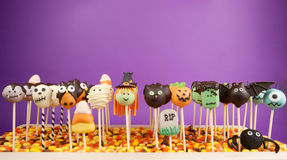 Halloween cake pops. Halloween mini cakes on sticks against purple background Royalty Free Stock Photo
