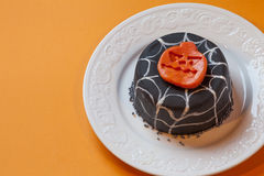 Halloween cake in a white plate. Surface orange background. A small cake for the holiday of Halloween. Pumpkin shape on the top of the cake. Decorative spider Royalty Free Stock Images