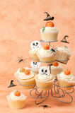 Halloween Cakes With Floating Witches Hats. Halloween cupcakes with a selection of festive toppings including floating witches hats Stock Image