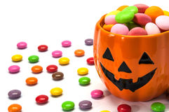 Halloween candies and pumpkin cup. Over white background stock images