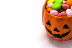 Halloween candies in pumpkin cup. Over white background stock photos