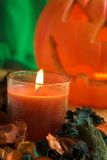 Halloween candle and light. Scented candle with potpourri and a pumpkin light Stock Photography