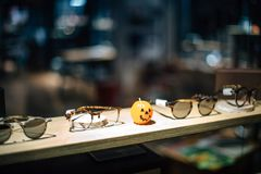 Halloween candle in shape of pumpkin between eye-war spectacles. And sunglasses during Halloween holiday Stock Photos