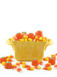 Halloween Candy. In a yellow dish, candy corn, candy pumpkins, spilling out on white vertical background, copy space stock images