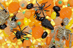 Halloween candy. Background with jellies, candy corn, and toy spiders and skeletons Stock Photos