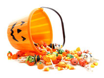 Halloween candy. Halloween jack-o-lantern pail with spilling candy over white Stock Image