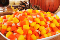 Halloween Candy. Close up of a bowl of candy corn on a table with a pumpkin centerpiece royalty free stock image