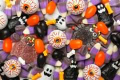 Halloween candy background. Halloween background of mixed candies, dark color theme Stock Images