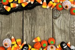 Halloween candy and black cloth double border against rustic wood Royalty Free Stock Photography